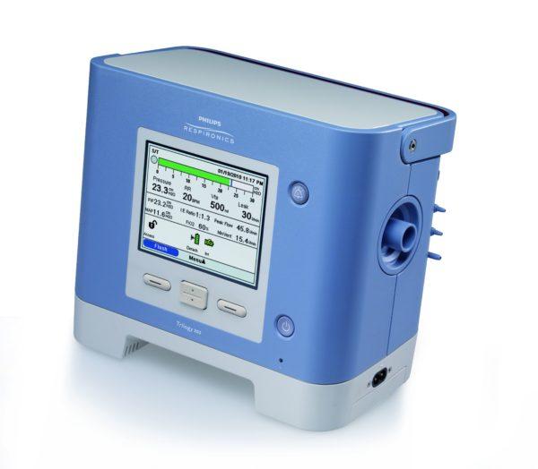Das Beatmungsgerät Philips Respironics Trilogy 202 wird von vorne dargestellt. Sein Display zweigt die gemessenen Atmungsparameter an. Frontalansicht