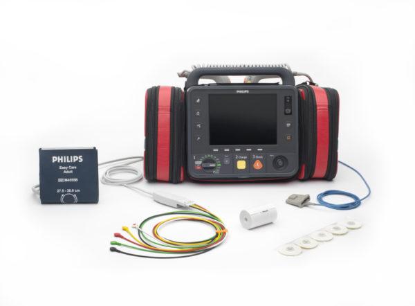 867172-Der Philips HeartStart Intrepid ist in diesem Foto inklusive Zubehör (z.B. Blutdruckmanschette, EKG-Kabel, SPO2-Sensor) dargestellt. Das Zubehör kann in den roten seitlich angebrachten Taschen verstaut werden.